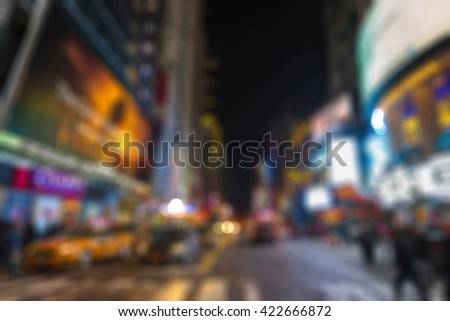 Blurred vision of 42nd Street in New York City, reflecting the ads, lights, crowds, taxis, traffic of cars and visitors in Times Square area in Manhattan. - stock photo