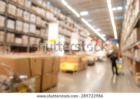 Blurred warehouse or storehouse background with some people - stock photo