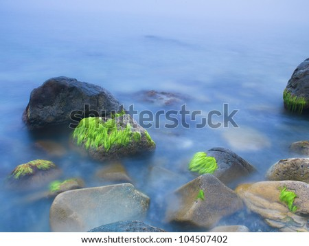 blurred water among sea cliff at sunrise; south italian beach