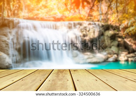 blurred waterfall and wood pier, beautiful waterfall in autumn forest, Kanchanaburi province, Thailand - stock photo