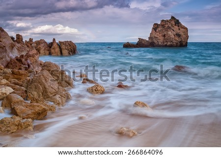 Blurred waves running down the beach. Beautiful landscape before the storm. - stock photo
