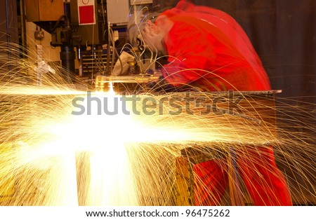 Blurred welder busy in workshop manufacturing metal construction. Many sparks shower from the torch. - stock photo