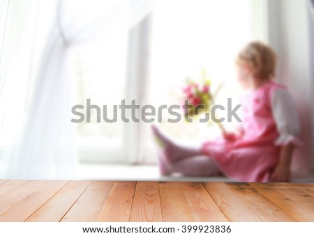Blurred window and little girl, wooden background - stock photo
