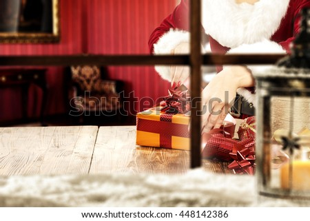 blurred window sill with snow and lamp with gifts and wooden table place