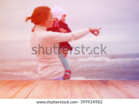 Blurred woman and kid at sea with wooden background - stock photo