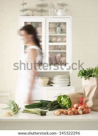 Blurred woman by vegetables on kitchen counter and utensils in cupboard - stock photo