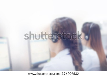 blurred woman call centrer working, work at computer display inside office room, technology concept. - stock photo