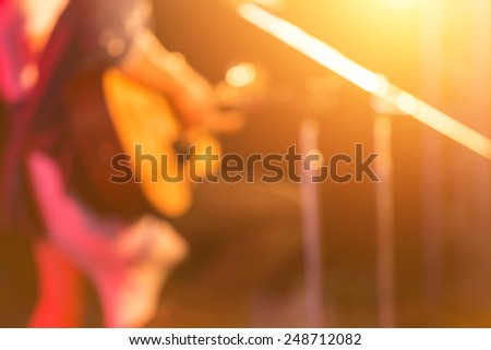 blurred woman guitar player on concert stage - stock photo