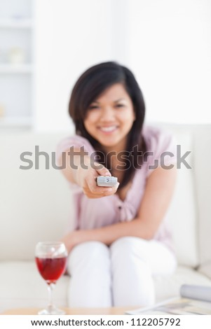 Blurred woman holding a television remote while sitting on a couch in a living room