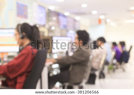 blurred woman/man operator working or searching on computer at office room:blur of woman monitoring and talking on headphone concept:blurry of people,business,technology :call centre help desk concept - stock photo