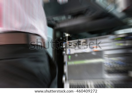 Blurred zoom of Asian man working on his computer server mainframe in a data center