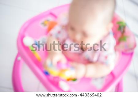 blurry baby in car walker - stock photo