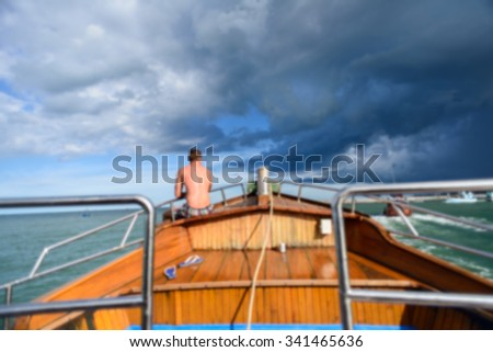 Blurry background man sitting on boat with big cloud.
