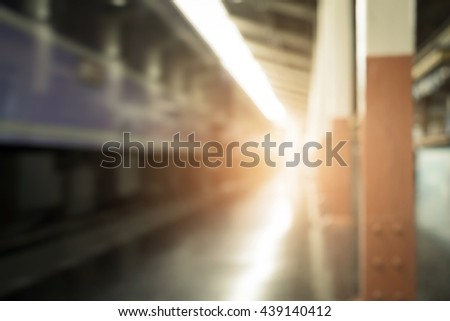 Blurry background of train station at sunset - stock photo