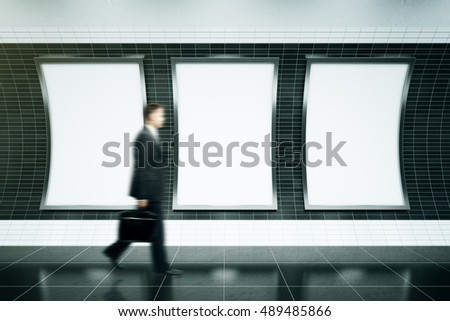 Blurry businessman walking in front of three empty ad posters in metro station with dark tile walls. Mock up, 3D Rendering