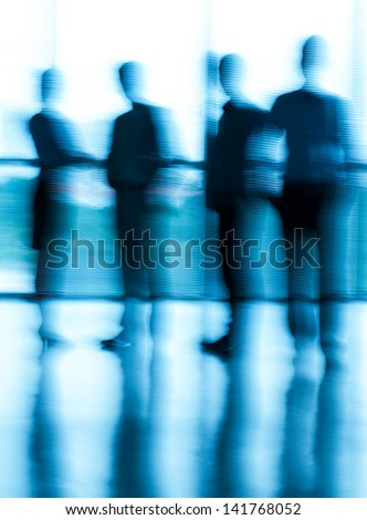 Blurry businesspeople standing at the office - stock photo