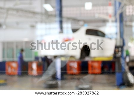 blurry cars on lifts in small service station for background - stock photo