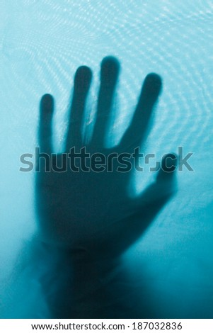 Blurry contour of hand behind blue fabric