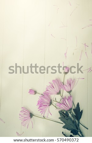 Blurry Flowers with shadow of wooden battens on white wooden table background on Valentine's Day times with copy space.