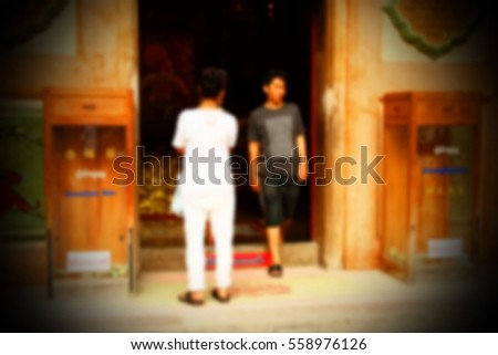 Blurry focus scene of people in front of the temple entrance.