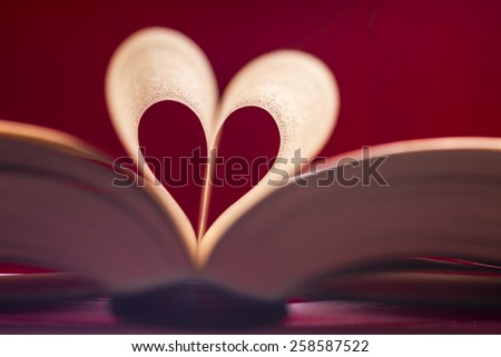 Blurry heart made from book pages over red background - stock photo