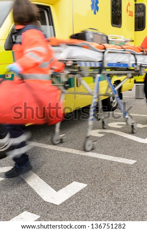 Blurry hurrying paramedics running to help with gurney - stock photo