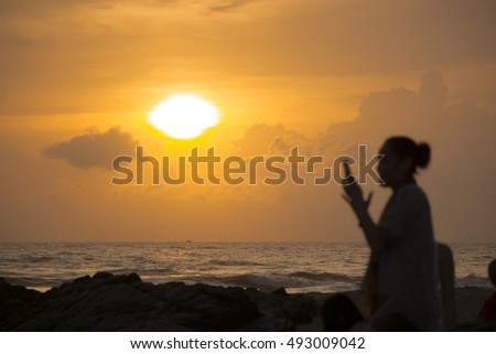 blurry image business woman using mobile phone on the beach at sunrise.