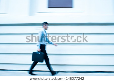 Blurry image of a walking businessman outside - stock photo