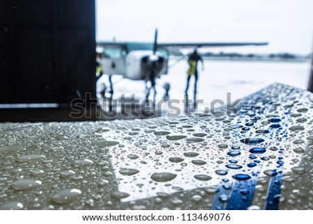 Blurry image of workers pulling the small plane into warehouse with wet plane wing as foreground - stock photo