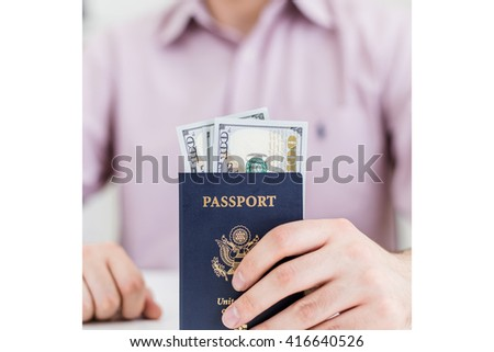 Blurry man in pink shirt sitting at white desktop with dollar banknotes inside american passport in hand - stock photo