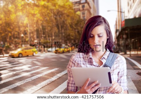 Blurry new york street against young focused student using a tablet computer - stock photo