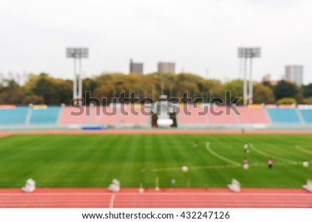 Blurry of football field in stadium on daylight. use for sport background.