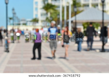 Blurry, out of focus abstract background image of people walking in a outdoor plaza in Key West, Florida.