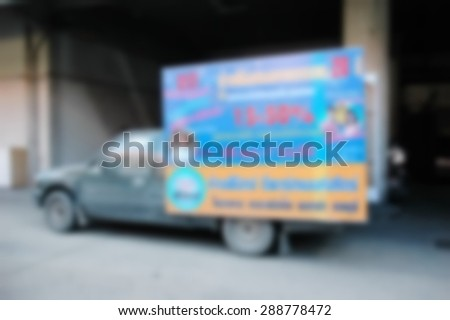 Blurry photo of light weight truck carry advertising board at the rear of car represent the media advertising concept related idea. - stock photo