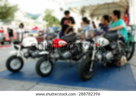 Blurry photo of man sit behind motorcycle on car booth selling area in the open market scene represent the people lifestyle concept related idea. - stock photo