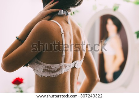 Blurry pose of a woman's sensual back wearing a white bra and looking in the mirror. Focus on the woman's back - stock photo