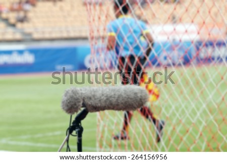 blurry Professional sport microphone on a football field with referee in the background - stock photo
