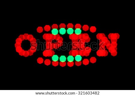 blurry red and green neon signboard with word open on black background - stock photo