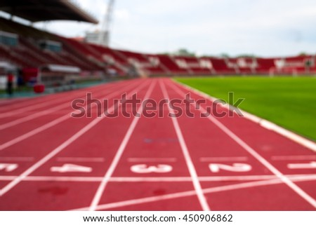 blurry red running track on the athletic stadium, out of focus . - stock photo