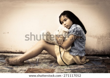 blurry sad asian girl alone sitting with white bear near old wall cement,vintage tone - stock photo