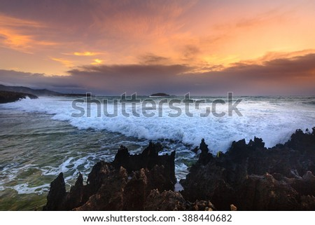 blurry waves over rocky beach at dawn with the beautiful sunrise