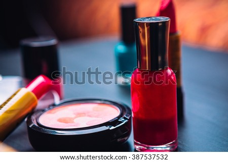 blush cosmetics nail  polish and lipstick on a dark wooden background - stock photo