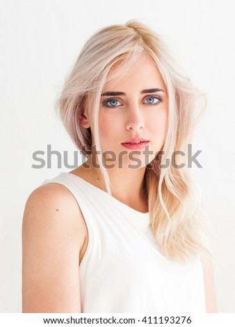 Blushed touching woman with nude makeup on white background. Blonde calm tender girl isolated on white. Fashion portrait of young beautiful girl in light studio.   - stock photo