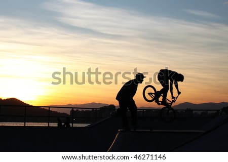 BMX Bike flying off the track with the sea, horizon and sunset in the background. Also shows the perfect silhouette of another guy looking amazed to the BMX. - stock photo
