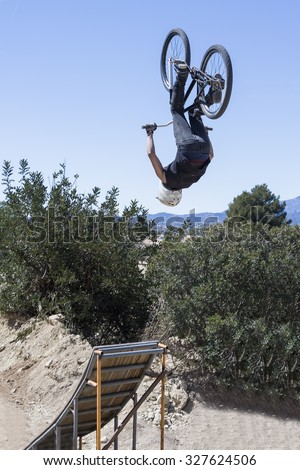 BMX biker performs high-flying BMX stunt with a BMX bike on a BMX session in the mountain - focus on the right leg - stock photo