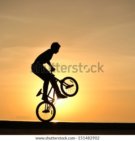 bmx rider action against sky at sunset. - stock photo