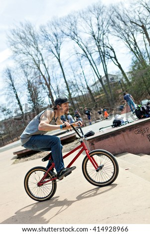 BMX rider athlete riding his bmx bike approaching a jump. - stock photo