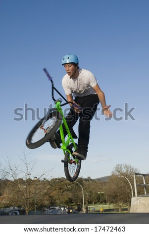 BMX rider jumps while doing bar spin - stock photo