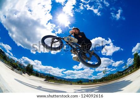 BMX rider jumps while doing cross bar trick. - stock photo