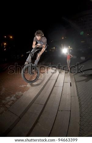 "BMX rider performing air trick ""bunny hop 180 bar-spin"" - stock photo"